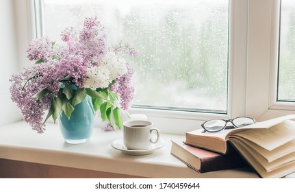 Bouquet of lilacs in a vase,cup of coffee and books on the windowsill. - Shutterstock ID 1740459644