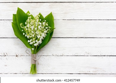 bouquet of lilies of the valley flowers with green leaves tied with twine in the water droplets on the white wooden boards. with space for posting information