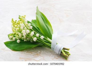 Bouquet of Lilies of the Valley isolated on marble background.