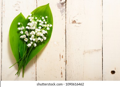 bouquet of lily of the valley flowers on old painted bright wood table background
