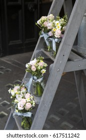 A bouquet of lisianthus, roses and carnations on the steps of the staircase as decoration of the entrance to the house