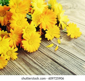 Bouquet from a marigold. Yellow summer flowers on a wooden surface. Calendula flowers. Holidays bouquet