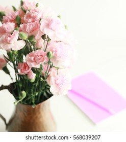 Bouquet of miniature pink carnations in a copper vase with a blurred pink notepad in the background.
