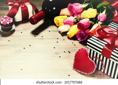 Bouquet of multicolor roses with decorative heart and presents. St Valentine's concept with copy space