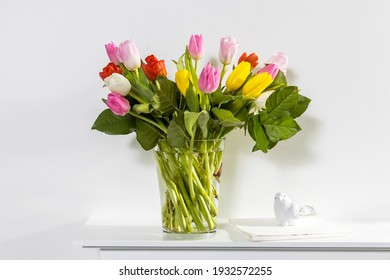 A bouquet of multi-colored tulips in a transparent vase and cup of tea on the white window.