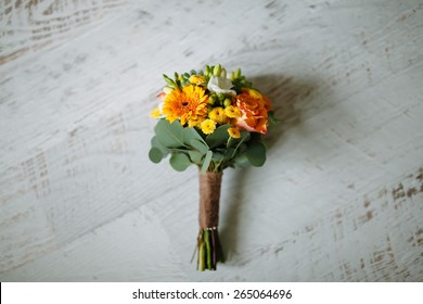 bouquet of orange flowers and green on a white wooden floor, wedding bouquet