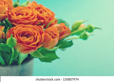 Bouquet of orange roses in a vase on vintage shabby chic background