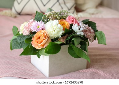 bouquet of orange and white flowers in a box stands on a pink background
