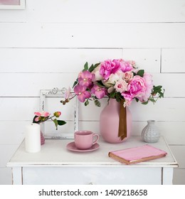 A bouquet of orchids, peonies, roses in a ceramic vase on the bedside table and a stack of books