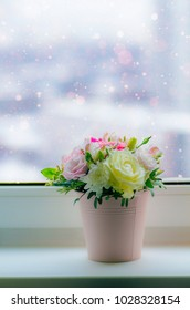 Bouquet in pastel colors and snow outside the window