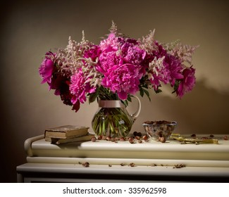 bouquet from peonies in glassy vase with old nutcracker and books on table on beige background