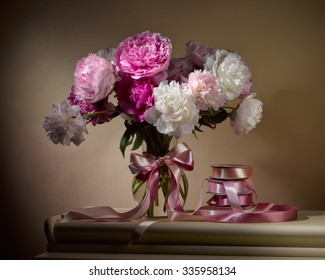 bouquet from peonies in glassy vase with satin ribbons on table on beige background