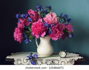 Bouquet of peonies and irises in a jug and an alarm clock on a blue background. Retro still life.