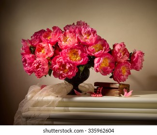 bouquet from peonies with old box with beads on table on beige background