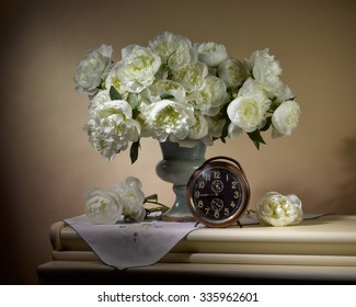 bouquet from peonies with old clock on table on beige background