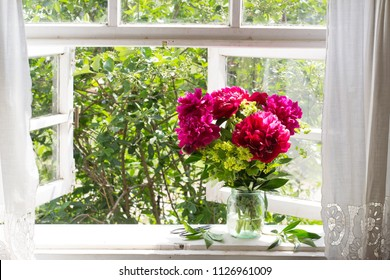 Bouquet of peonies on the windowsill