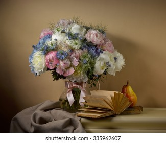 bouquet from peonies with opened book and pear on table on beige background