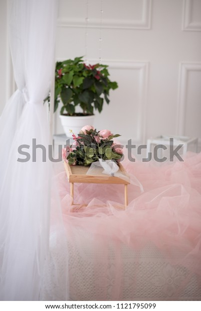 bouquet of peony bush with pink purple flowers and green leaves on a light pink background