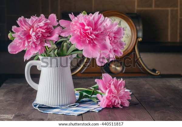 bouquet of peony flowers on old wooden table with clock