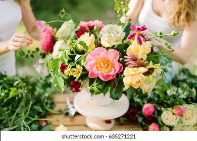 bouquet, people and floral arrangement concept - hands of two young woman drawing up a bouquet of beautiful roses, pink peonies, daisies in white vase, art workshop at wooden table in summer garden