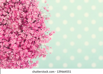 Bouquet of pink baby's flowers on turquoise dotted background with vintage editing