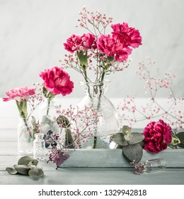Bouquet of pink carnation flowers in glass vase on light turquoise wooden background. Mothers day, birthday greeting card. Copy space. Toned.