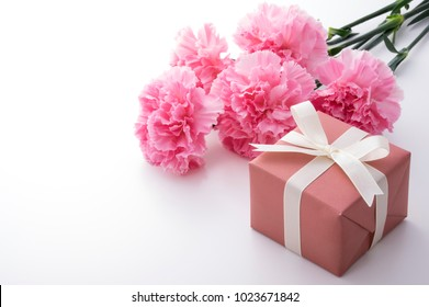 The bouquet of a pink carnation and gift box