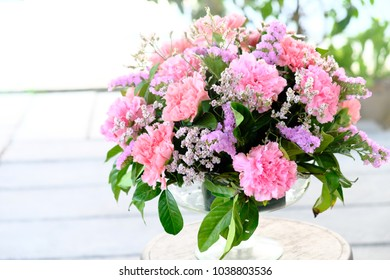 Bouquet of pink carnations flowers and green leaves in glasses vase on wooden table.