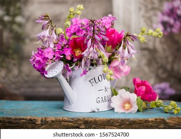 bouquet of pink flowers in a garden watering can