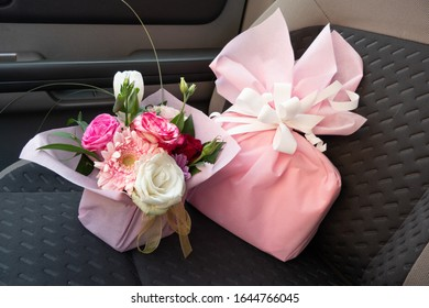 Bouquet of Pink Flowers and a Pink Present on a Car Seat