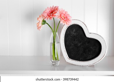 Bouquet of pink gerberas in glass vase with frame on a shelf over white wall background