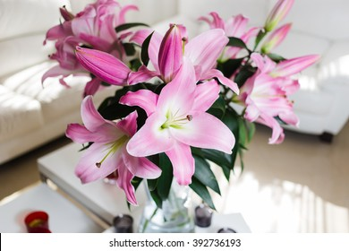 Bouquet of pink lilies in a glass vase indoors
