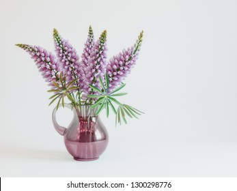 A bouquet of pink lupins with green leaves in a vase of pink glass on a white background. Rendered image.
