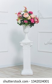 Bouquet of pink peonies. Flowers in white vase. The decor of the room with fresh flowers. Stucco work on the white walls. Spring photo zone. Vase on column.