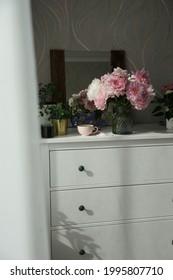 Bouquet de pivoines roses sur la commode dans la chambre