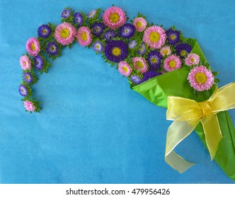 bouquet of pink and purple aster flowers in a green wrapping paper against blue background. Aster flowers arrangement.
