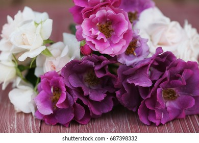 Bouquet of pink and purple garden roses on a wooden background