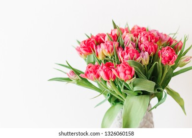 A bouquet of pink red white double peony tulips in a gray modern vase on wooden tabel. Happy mothers day. International women's day