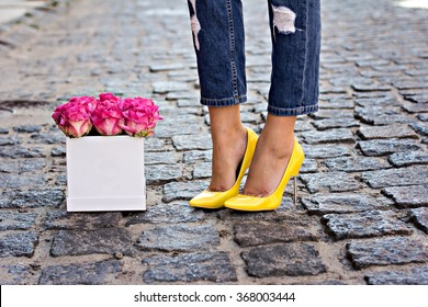 The bouquet of pink roses and female legs in jeans and yellow shoes with heels.