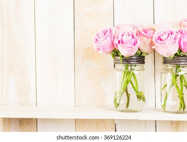 Bouquet with pink roses in mason jar on wood shelf.