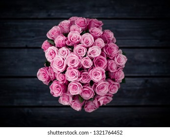 Bouquet of pink roses on dark wooden background