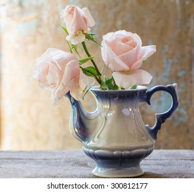 Bouquet of  pink roses in a  vintage teapot in rustic style