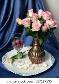 A bouquet of pink roses in a vintage wine jug on a vintage tray, a glass of red wine and black grapes.