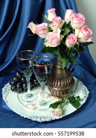 A bouquet of pink roses in a vintage wine jug on a tray, a glass of red wine and black grapes.