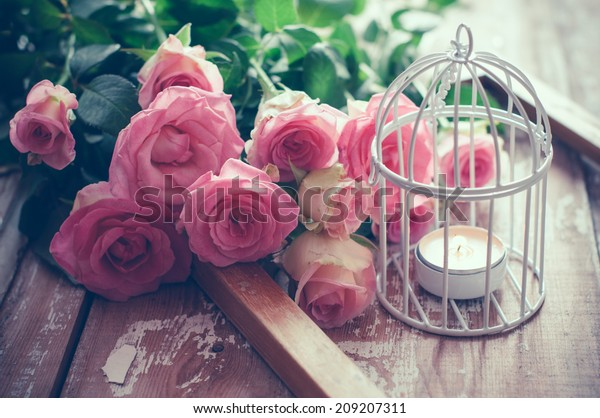 Bouquet of pink roses, wooden frame and a burning candle in a white decorative bird cage on old board background, vintage decor and color tinting
