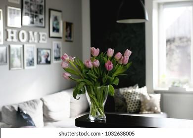 bouquet of pink spring tulips in glass vase in morning light in scandinavian living room