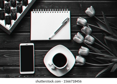 bouquet of pink Tulip flowers with a Cup of coffee and a box of chocolates for the morning Breakfast and an empty notebook with a smartphone. 3D virtual reality glitch effect