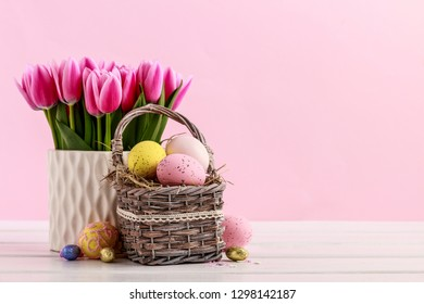 Bouquet of pink tulips and basket of Easter eggs. Postcard motif.
