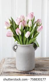 Bouquet of pink tulips in grey ceramic vase.