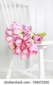 Bouquet of pink tulips lying on a chair.